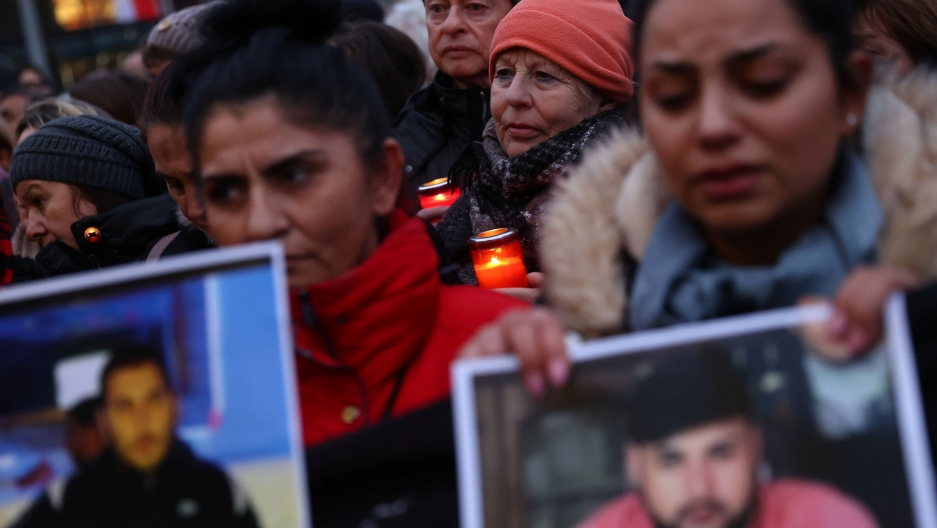 A large group of people are shown at a vigil with several holding candles and photographs.