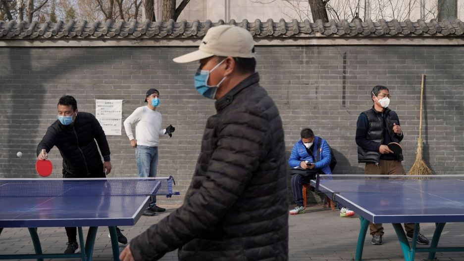 Several people are shown playing table tennis and wearing face masks.