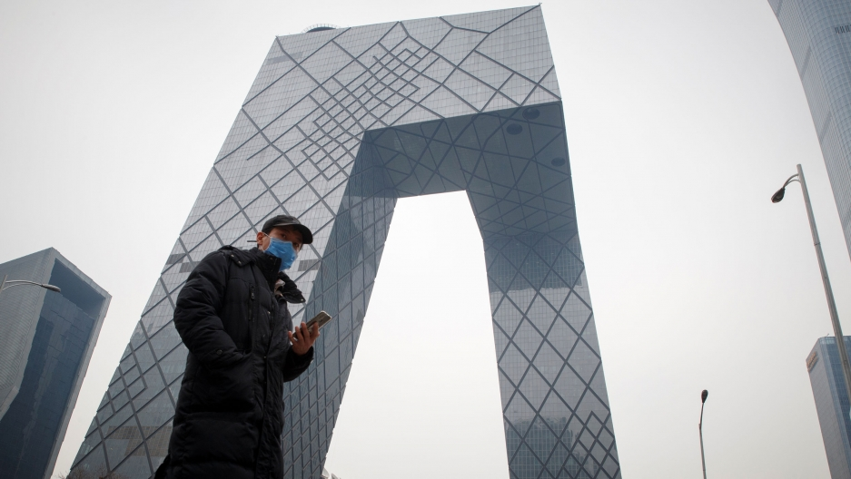 A man is shown standing in front of the CCTV headquarters building with a mobile phone and wearing a face mask.
