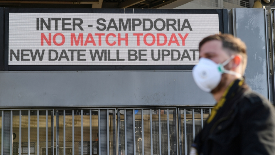 "A man is shown in soft focus wearing a face mask and standing outside the San Siro stadium with a sign that reads, ""No Match Today."""