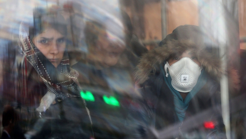 Women are shown through reflecting glass with one wearing a face mask and a hooded jacket.