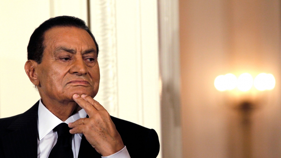 Hosni Mubarak is shown in a close up photograph looking to his left with his chin resting on his hand.