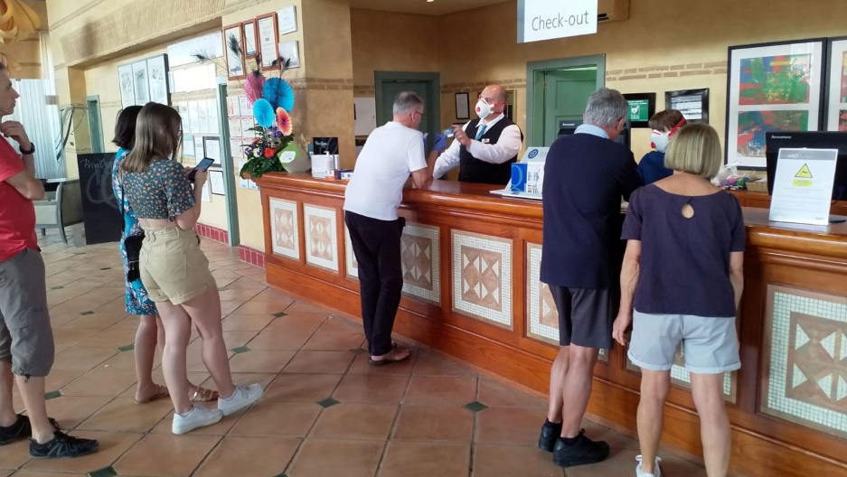 "Several people are shown standing at the counter of a hotel resort with the words, ""Check out"" on a sign behind the counter."