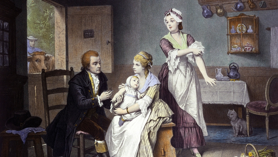 Edward Jenner, vaccinating his young child, held by Mrs. Jenner; a maid rolls up her sleeve, a man stands outside holding a cow. Coloured engraving by C. Manigaud after E Hamman.