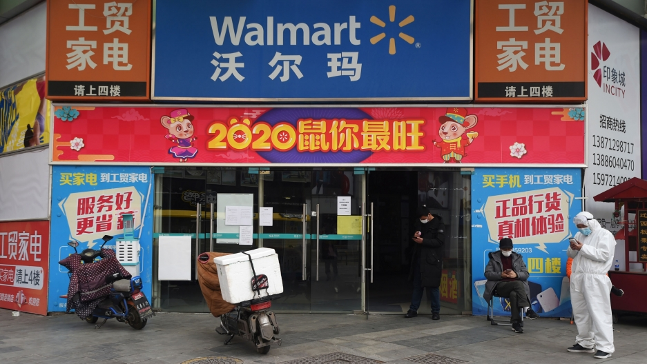 A colorful entrance to a Walmart in Wuhan, China, is shown with several advertisements and two men nearby wearing face masks.