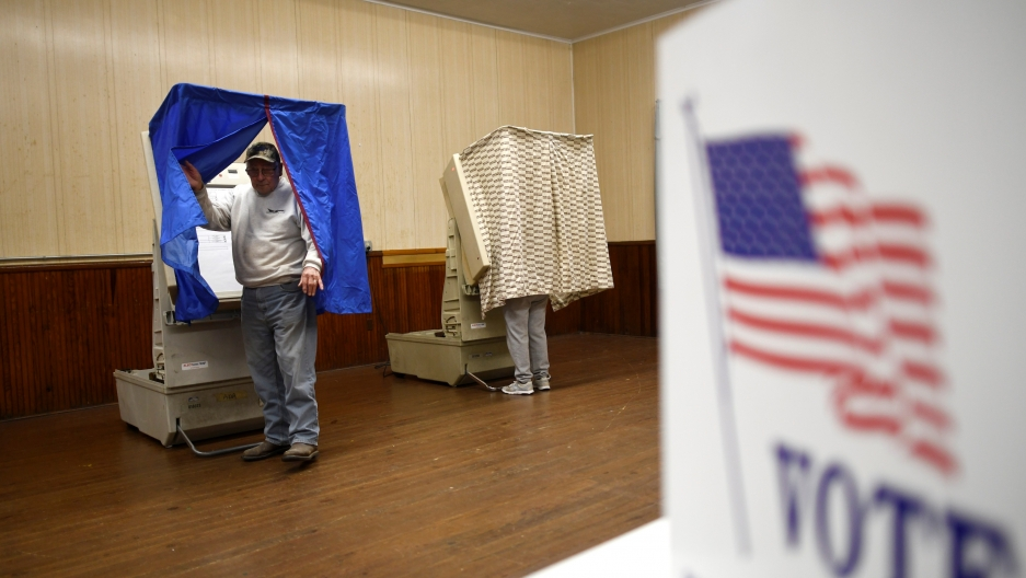 A man leaves a voting booth