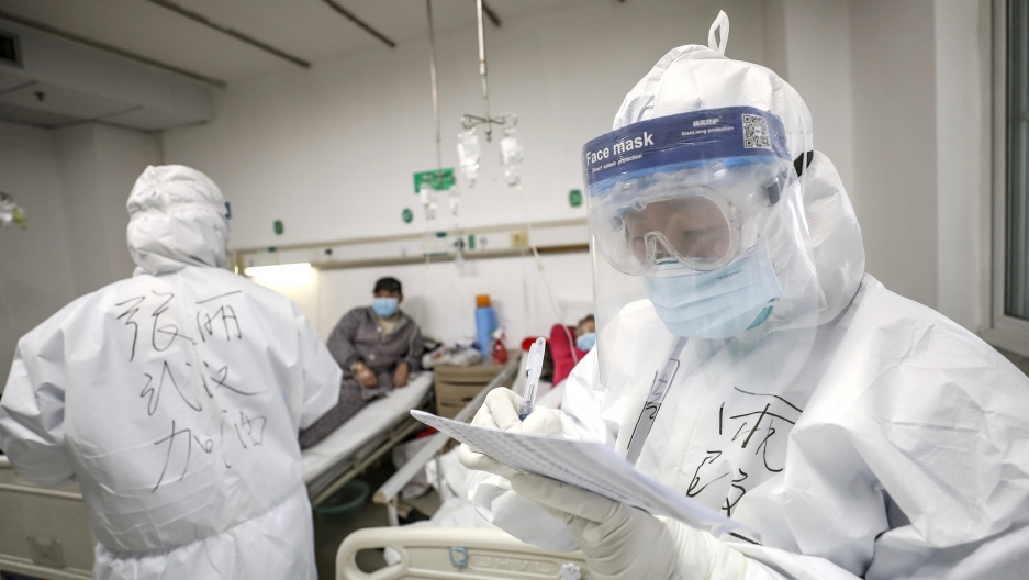 A medical worker in protective suit checks a patient's records at Jinyintan hospital in Wuhan, the epicentre of the novel coronavirus outbreak, in Hubei province, China, Feb. 13, 2020.