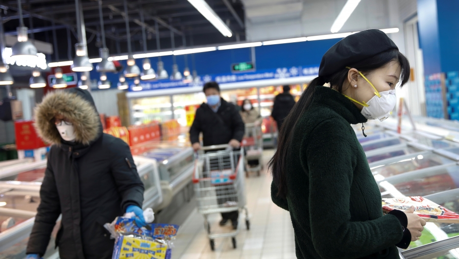 People wearing face masks look for products at a supermarket, as the country is hit by an outbreak of the new coronavirus, in Beijing, Feb. 19, 2020.