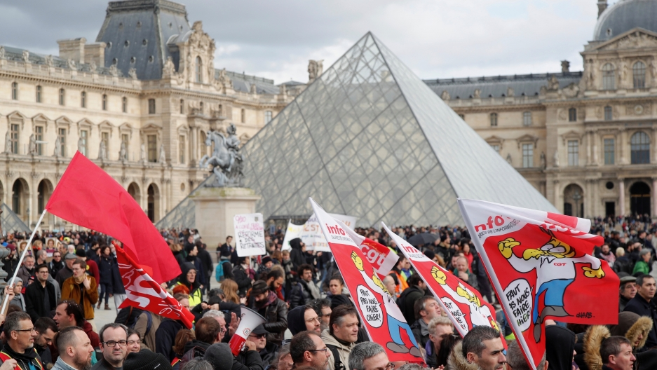 Protesters attend a demonstration in front of the glass pyramid of the Louvre museum before the opening debate on the French government's pensions reform bill at the National Assembly in Paris, Feb. 17, 2020.