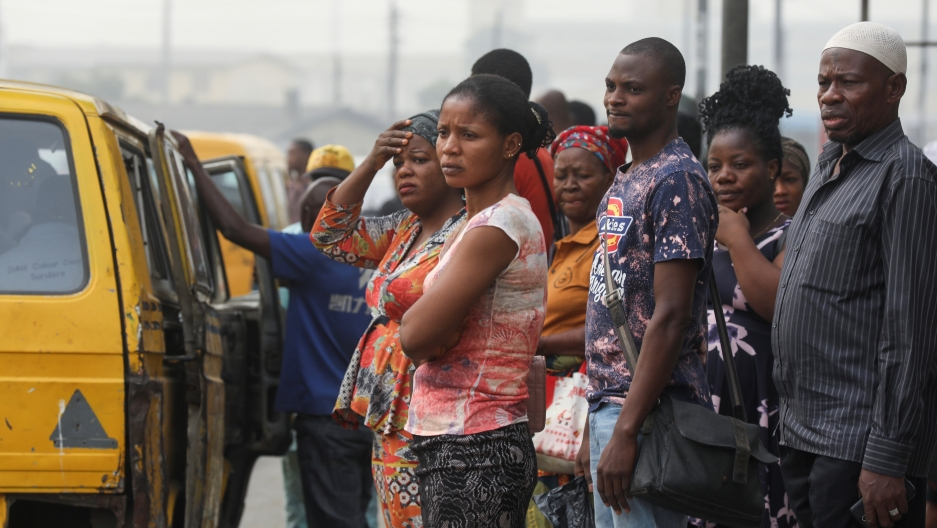 People are seen waiting for a bus at a bus-top in Lagos, Nigeria, Feb. 13, 2020.