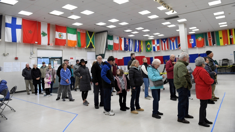 Voters wait in line to cast their votes at the Bicentennial Elementary School in New Hampshire's first-in-the-nation US presidential primary election in Nashua, New Hampshire, Feb. 11, 2020.
