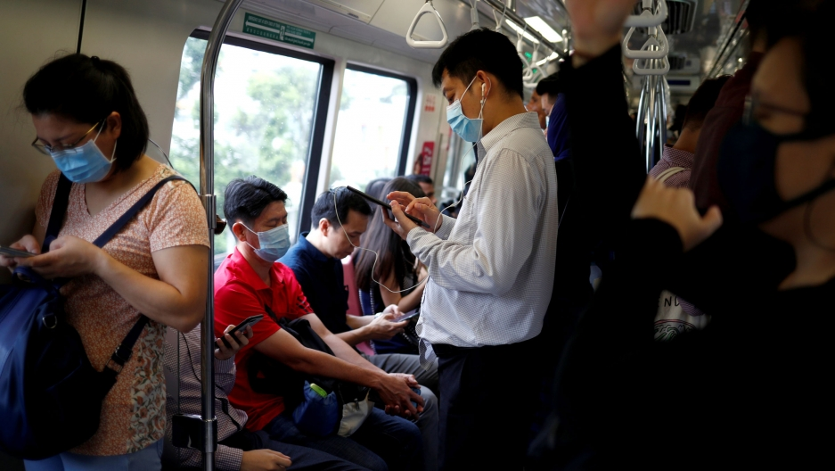 Commuters wearing masks in precaution of the coronavirus outbreak are pictured in a train during their morning commute in Singapore, Feb. 18, 2020.