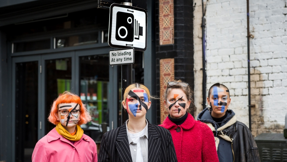 Four people with painted faces stand in front of a street sign with a camera on it.