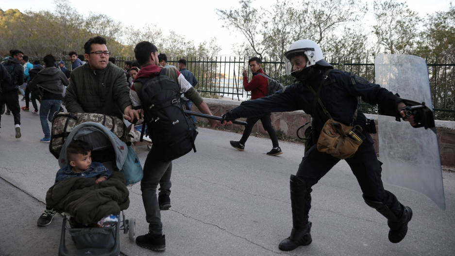 A riot police officer hits a migrant with his baton as police tries to disperse a group of migrants outside the port of Mytilene,Greece, March 3, 2020.