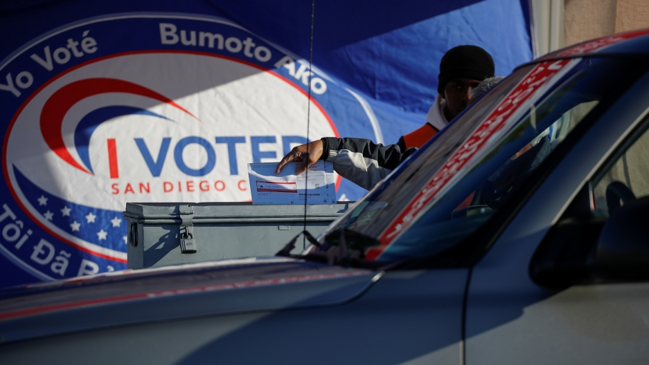 A poll worker drops in drive-through ballots into a ballot box as fourteen states including California hold primaries on Super Tuesday in San Diego, California, on March 3, 2020.
