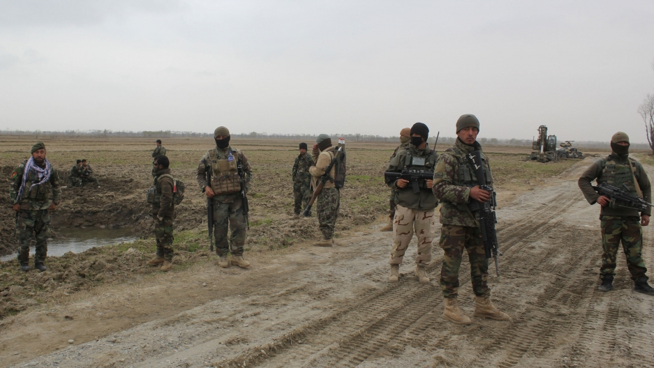 A group of soldiers are shown wearing fatigues and carrying weapons while standing in a dirt road.