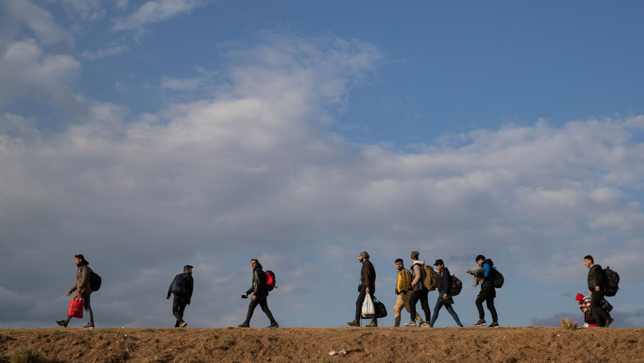Several people are shown from a distance walking in a line and carrying their belongings.