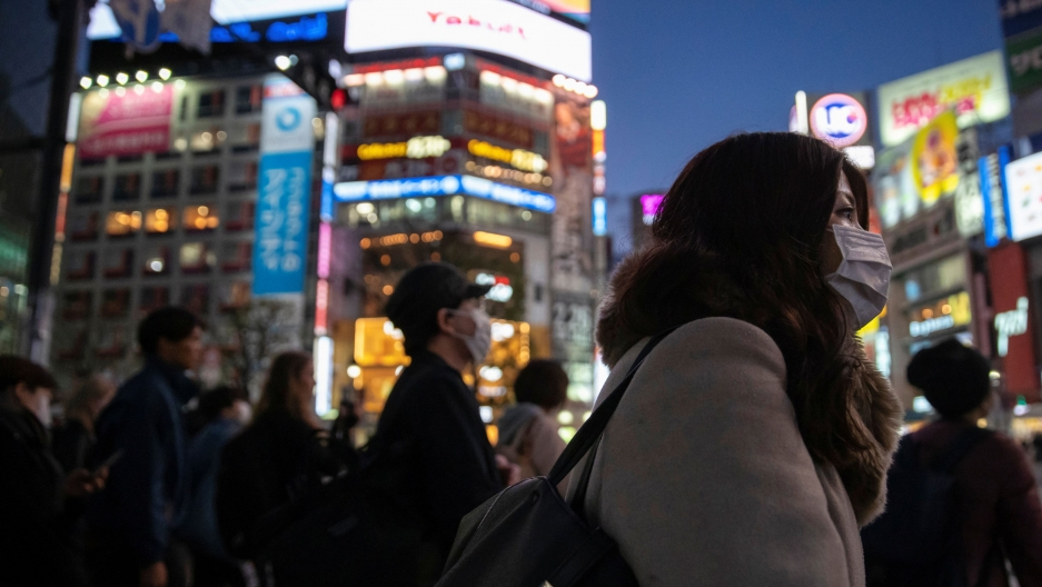A large group of people are shown crossing an intersection, most wearing face masks, with brightly lit buildings in the background.