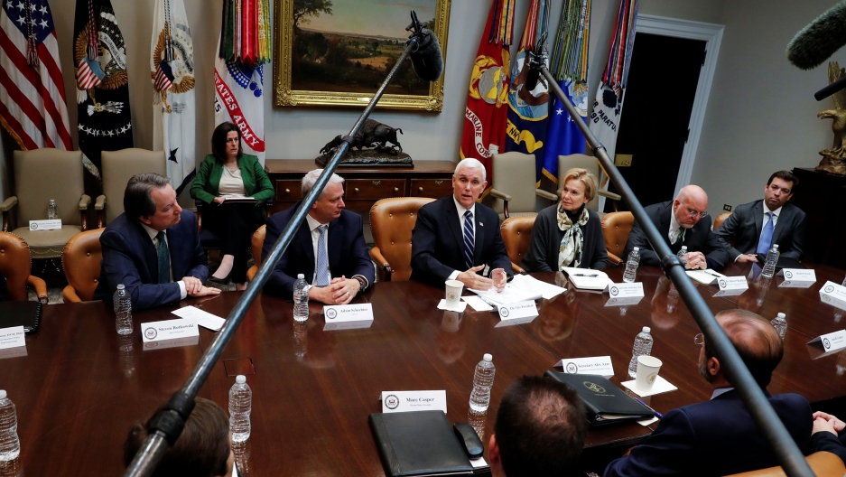 US Vice President Mike Pence is shown sitting at a table with people sitting all around him and microphones on boom polls hanging overhead.