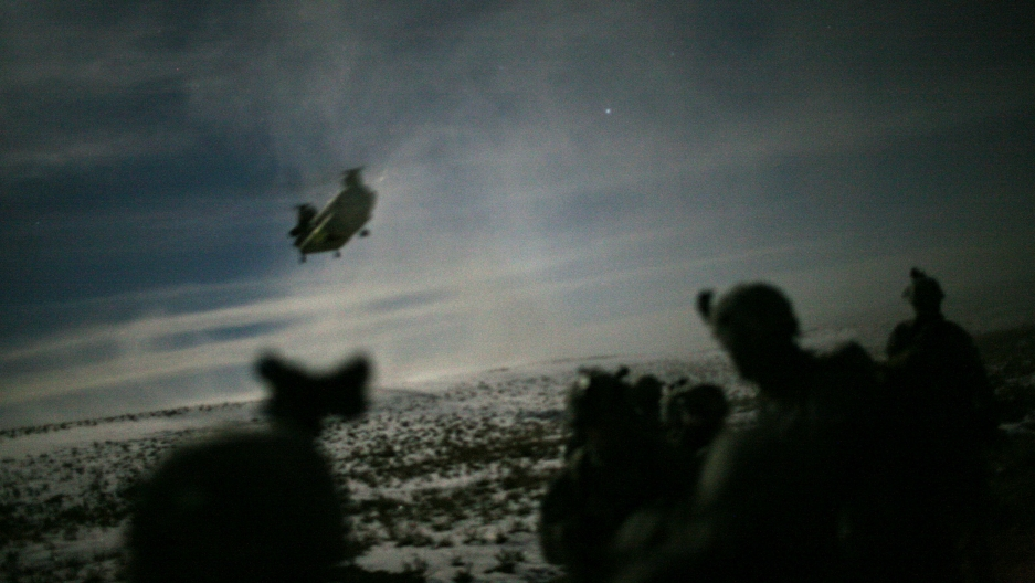 A large helicopter is shown in the distance making its landing approach with the shadow of soldiers in the nearground.