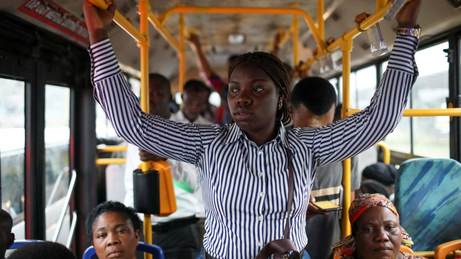 A young woman is shown standing in the middle aisle of a bus holding on to yellow handles.