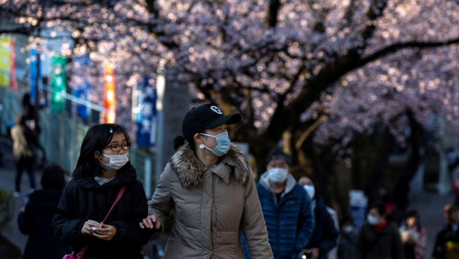 Several people are shown wearing face masks and walking near the pink blossoms of cherry trees.