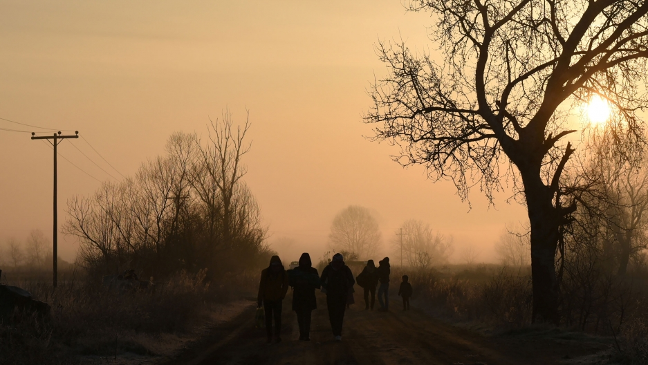 Several people are shown in shadow walking along a road with trees on either side.