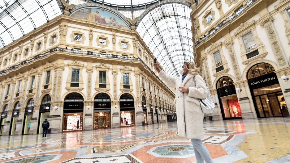 A woman is shown wearing a white jacket and a face mask is shown standing in the middle of the Galleria Vittorio Emanuele II taking a photograph.
