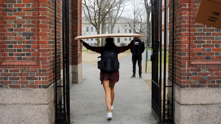 A student carries a box to her dorm at Harvard University