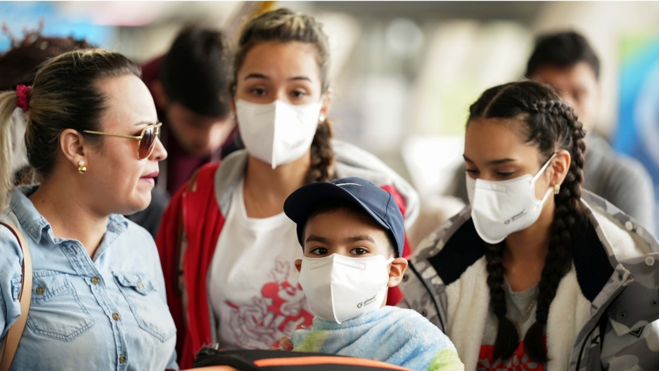 A family wearing face masks queues in a check-in line at Dulles International Airport a day after US President Donald Trump announced travel restrictions on flights from Europe to the United States for 30 days to try to contain the coronavirus, in Dulles.