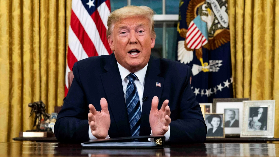 President Donald Trump is shown sitting at desk speaking with his hands outstretched.