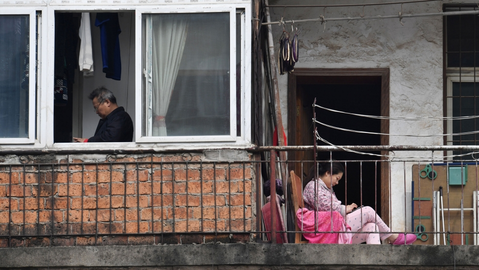 A woman is shown sitting and wearing pink while looking at her mobile phone adjacent to a man shown through an open window.