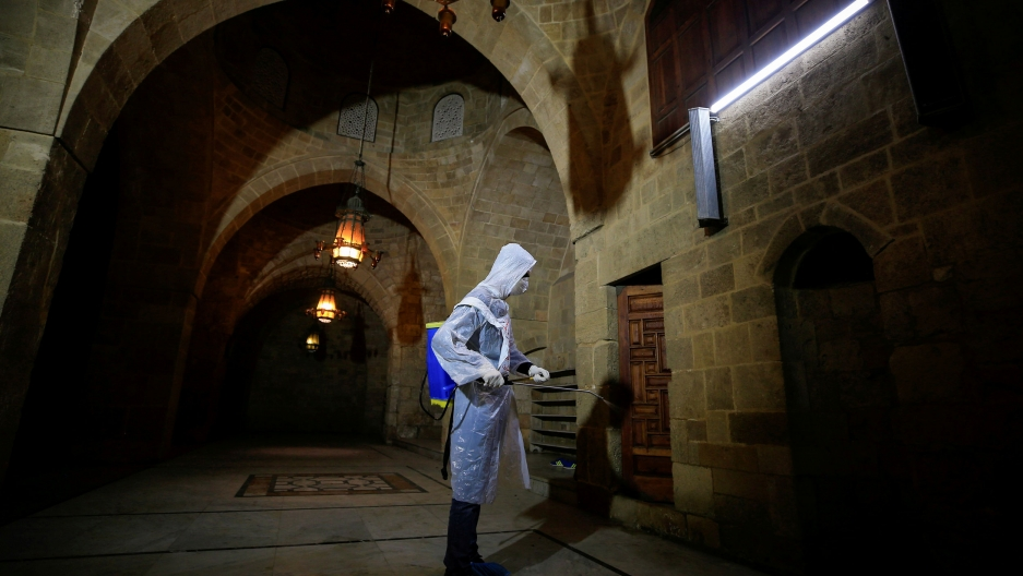 A volunteer in protective gear sanitizes a mosque