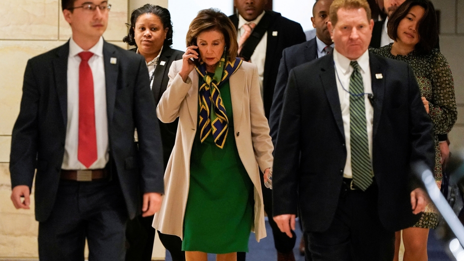 Speaker of the House Nancy Pelosi is shown walking amongst a group of people and wearing a green dress and khaki jacket while speaking on the phone.