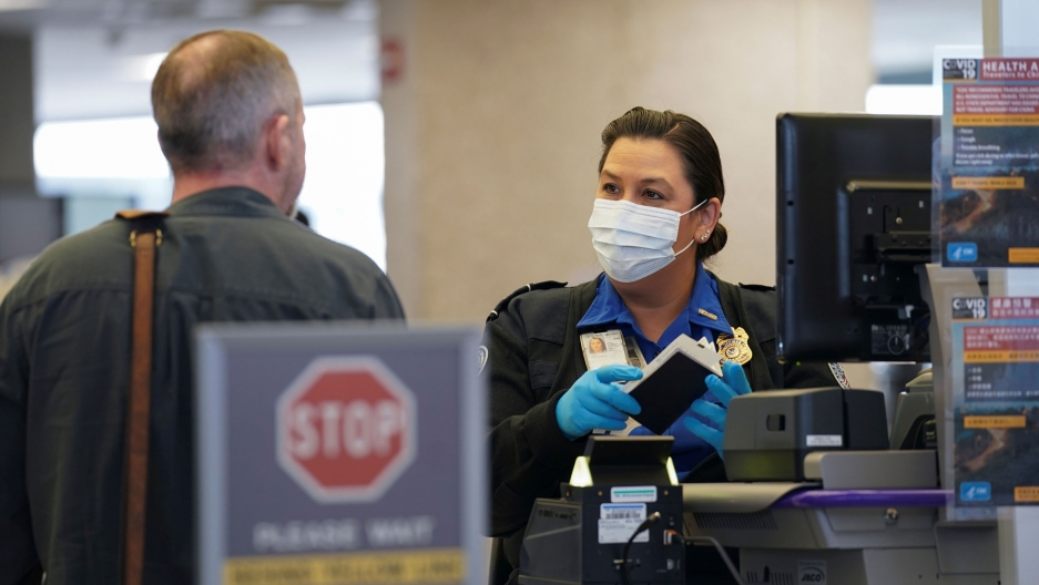 A TSA officer wearing a face mask clears a departing passenger