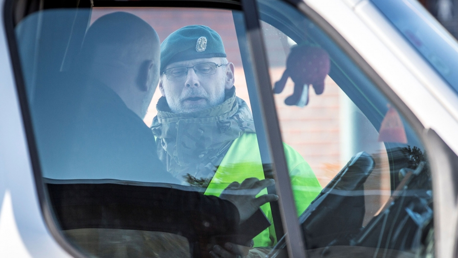 A police officer checks a driver at the Danish border in Rodby,Denmark, March 14, 2020.
