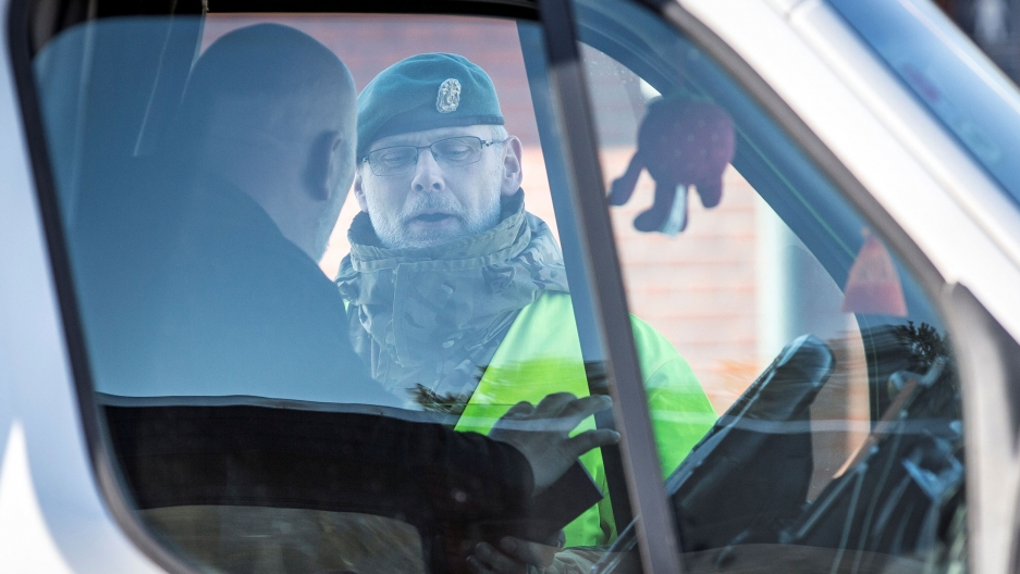 A police officer is shown through the windows of a truck with the driver looking at the officer.
