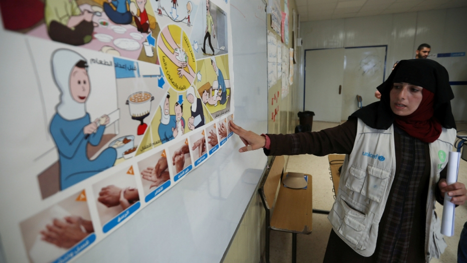 A woman shows washing hands instructions to students in a classroom.