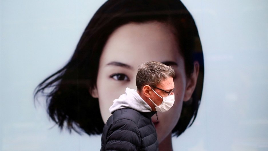 A man is shown wearing a puff jacket and face mask and walking past a advertisement with the face of a woman on it.