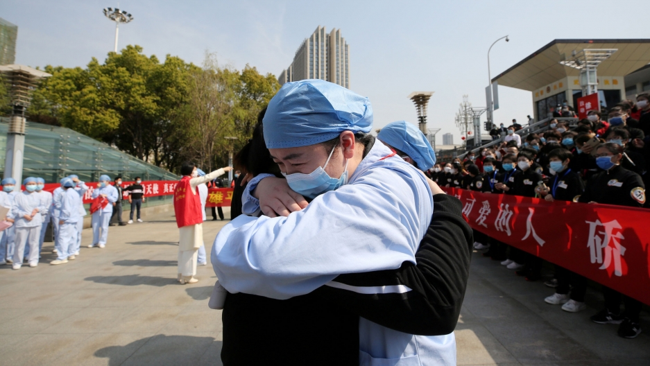 A man wearing a face mask and protective clothing is shown hugging another person in the street.