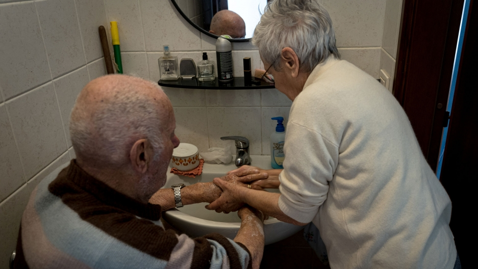 And older woman washes an older man's hands