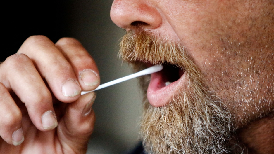 a close up of a man with a beard swabbing his mouth.