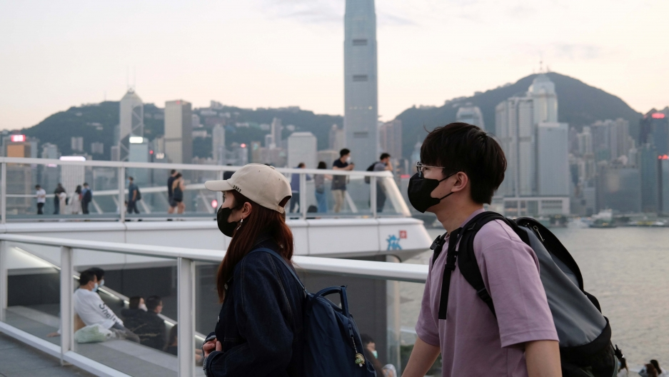 People with protective masks walk in front of Hong Kong's skyline, following the novel coronavirus disease (COVID-19) outbreak, China March 23, 2020.