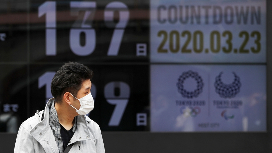A man is shown wearing a face mask and walking in front of a countdown clock for the 2020 Olympics Games in Tokyo.