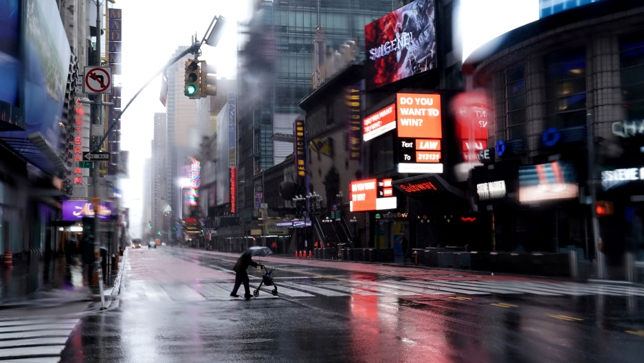 A person with a walker crosses and carrying an umbrella is seen crossing 42nd Street with brightly lit signs all around.
