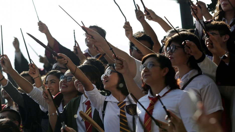 A large group of people are shown dressed in the Harry Potter white button down shirts and stripped ties while holding wands in the air.