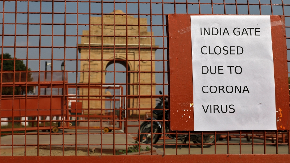 A close-up photograph of a reddish metal gate with a motorcycle parked behind it and the India Gate war memorial is shown off in the distance.