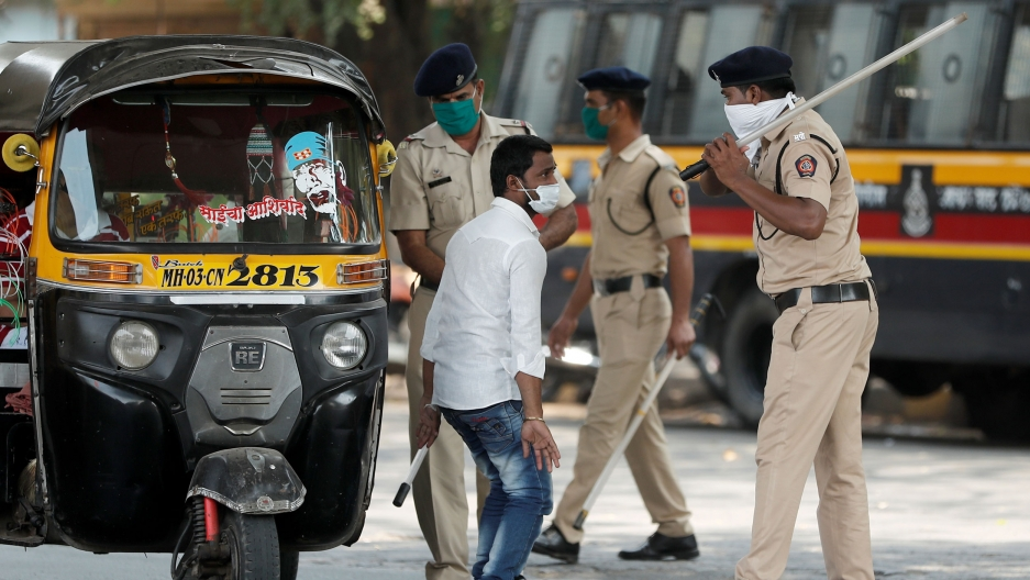 A man is shown standing near a auto rickshaw with several police officers standing by and one holding a long baton in the air.