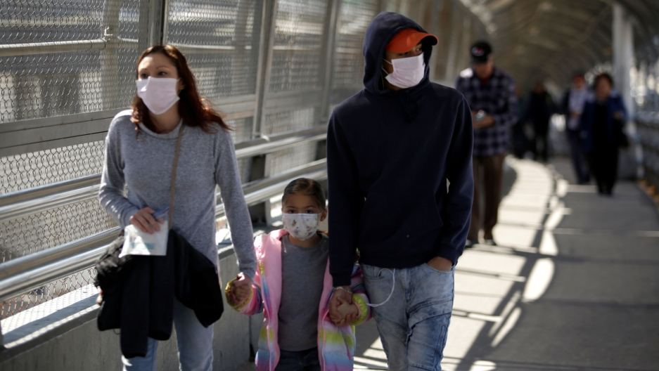 A family wearing protective face masks walks toward the US at the Paso del Norte International Border bridge.