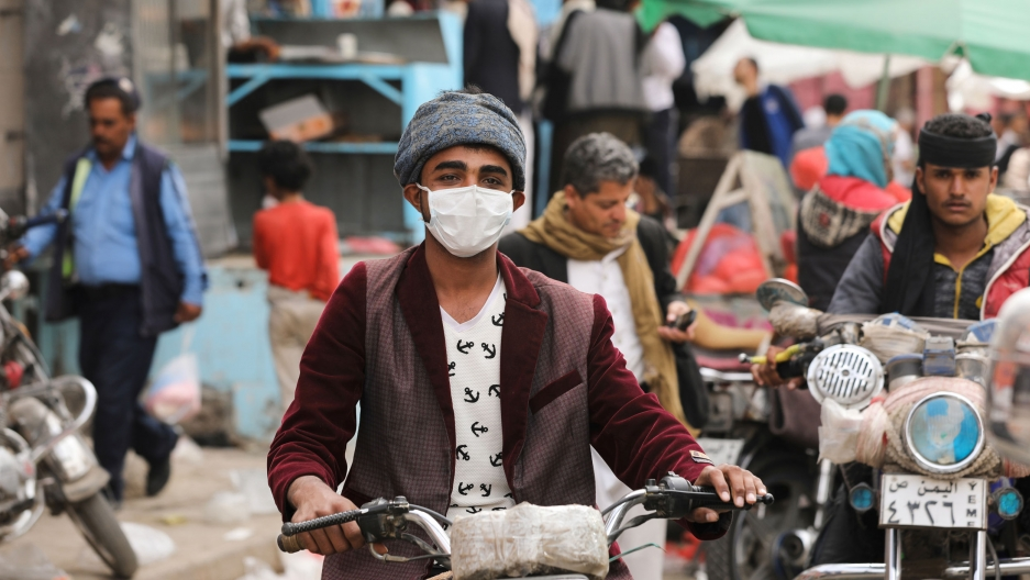 A man wears a protective face mask as he rides a motorcycle